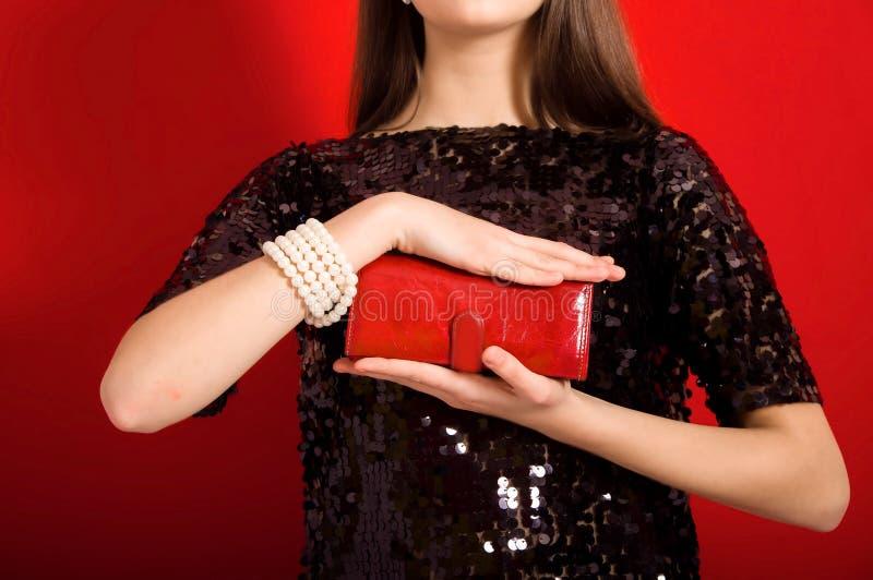 Härlig flicka med en röd kopplingpåse royaltyfri fotografi