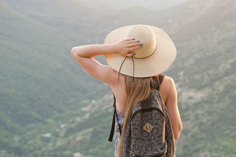 Härlig flicka med en ryggsäck och ett brett hattanseende med henne tillbaka mot en bakgrund av gröna berg royaltyfri fotografi