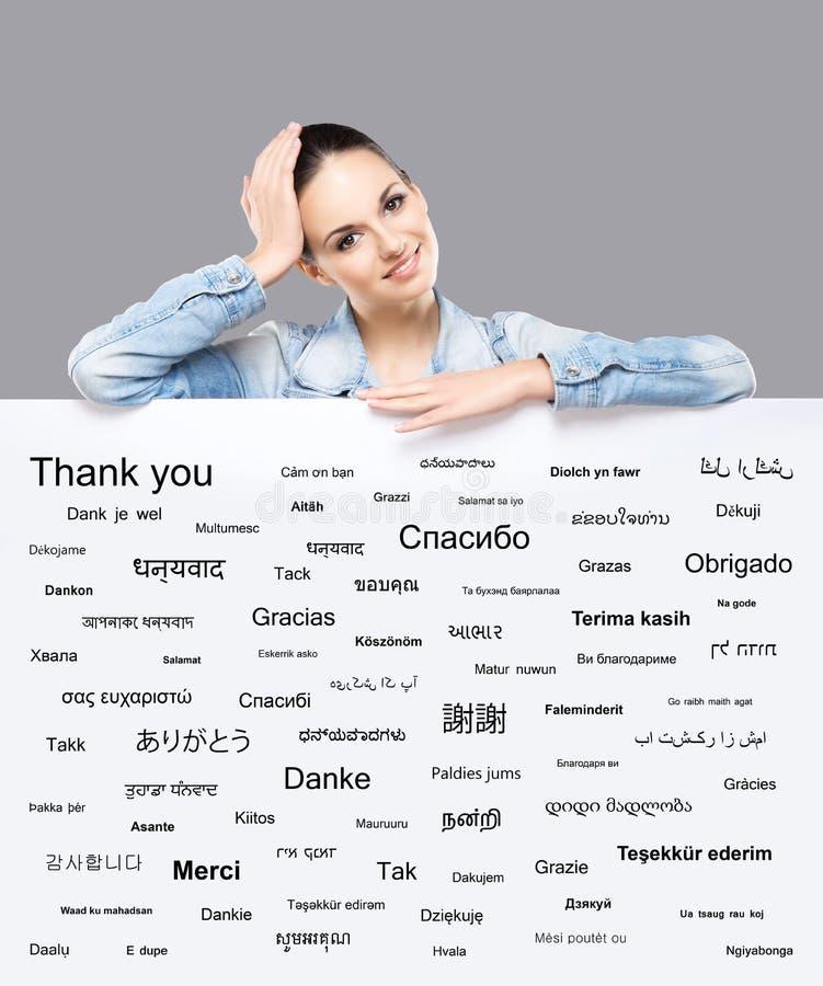 Härlig flicka med ett baner av världs olika språk royaltyfri bild