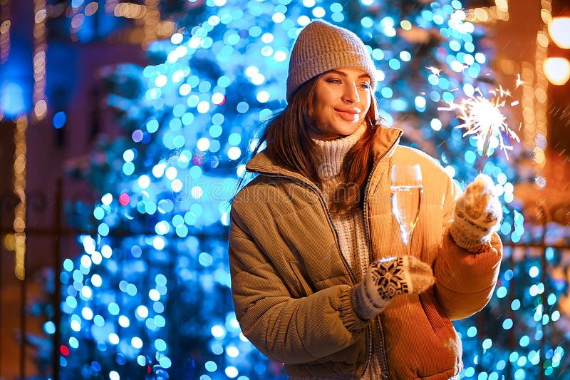 Härlig flicka med ett exponeringsglas av champagne och gnistrandet i den öppna luften på bakgrunden av julträdet i en vinter fotografering för bildbyråer