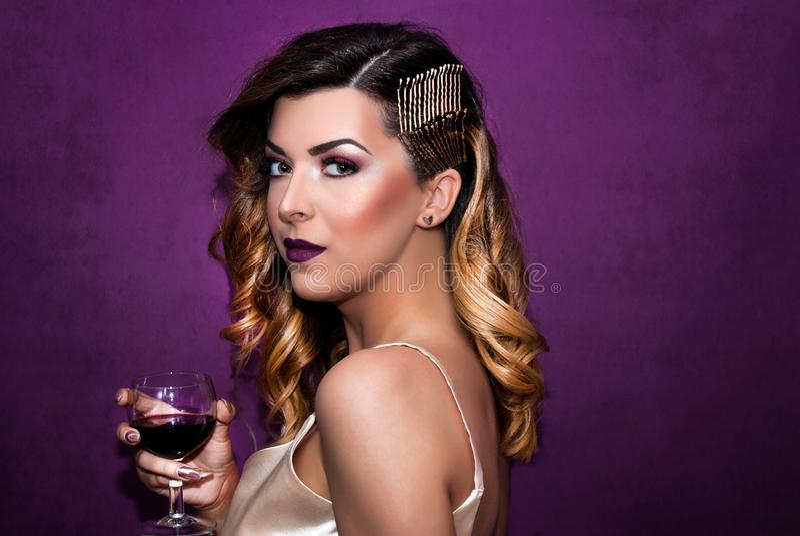 Härlig flicka med ett exponeringsglas av vin i hand med den lockiga guld- frisyren som framme poserar av den purpurfärgade väggen arkivbild