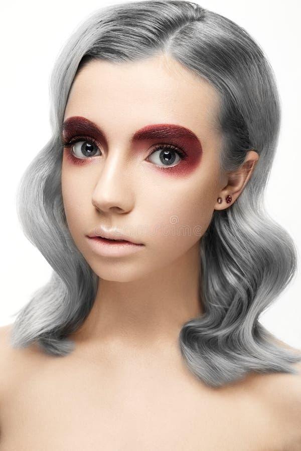 Härlig flicka med ett grått krullningshår och en idérik makeup Härlig le flicka arkivbild