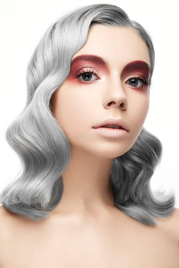 Härlig flicka med ett grått krullningshår och en idérik makeup Härlig le flicka arkivbilder