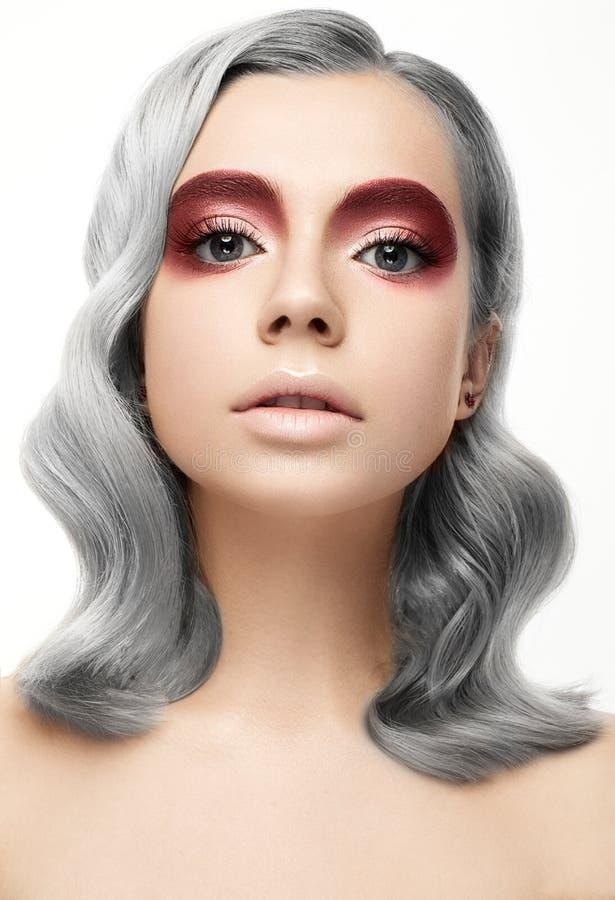 Härlig flicka med ett grått krullningshår och en idérik makeup Härlig le flicka royaltyfri fotografi