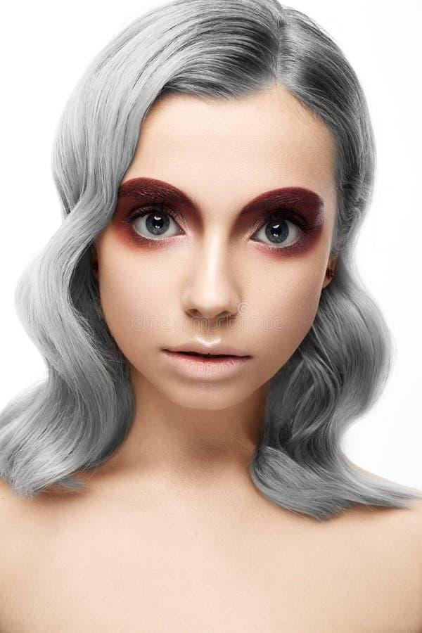 Härlig flicka med ett grått krullningshår och en idérik makeup Härlig le flicka arkivfoton