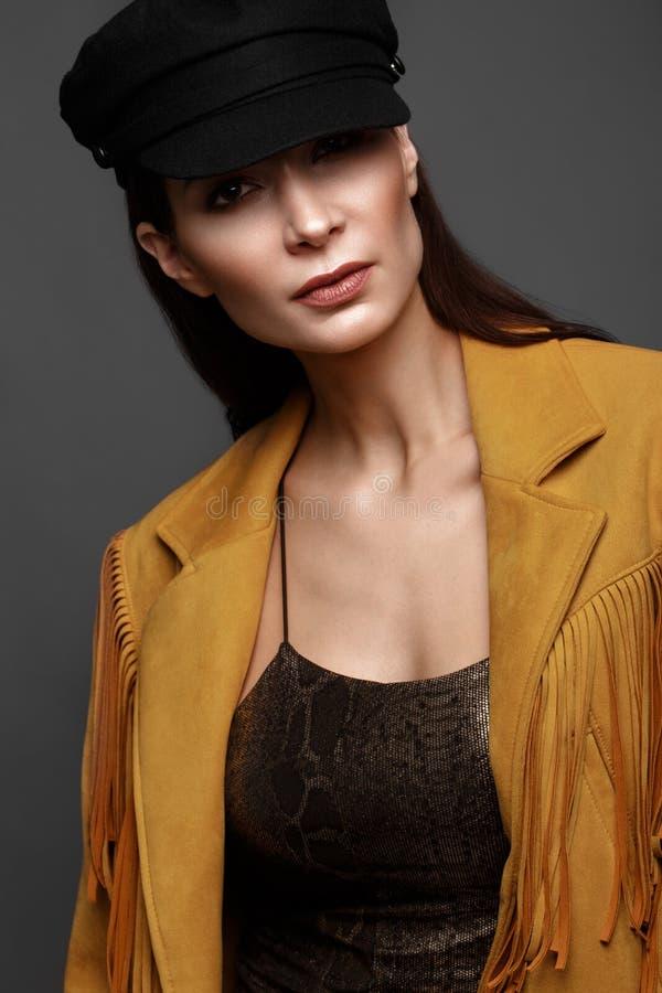 Härlig flicka med ett klassiskt smink och en frisyr i ett trendigt märkes- omslag och lock som poserar i studion arkivbilder