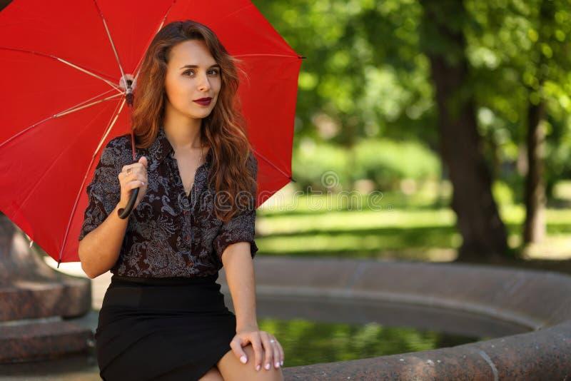 Härlig flicka med ett rött paraply på kanten av springbrunnen royaltyfri bild