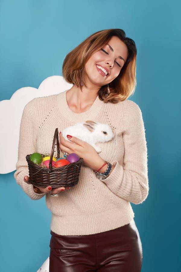 Härlig flicka med för för påskkanin och färg för korg vita ägg arkivbilder