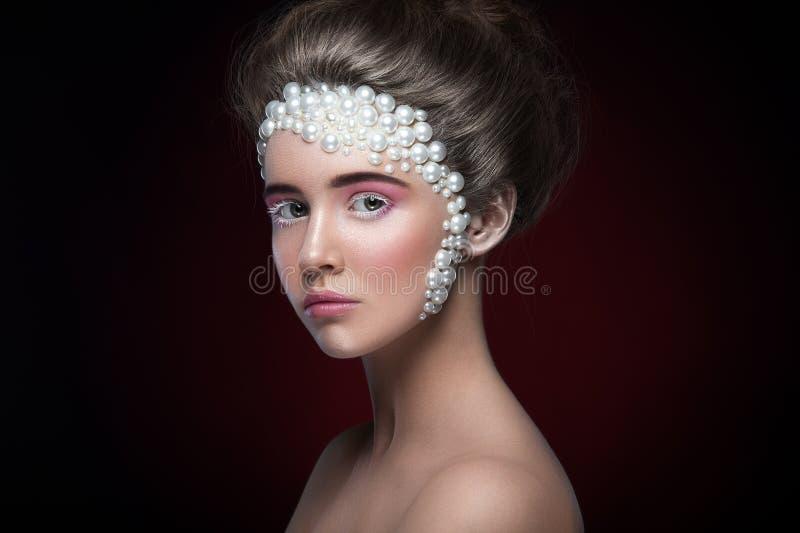 Härlig flicka med fantastiskt smink och pärlor och rosa färgöga-skuggor royaltyfria foton
