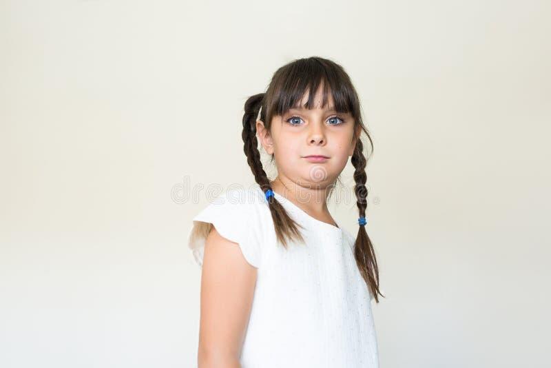 Härlig flicka med flätat hår som ser kameran royaltyfri bild