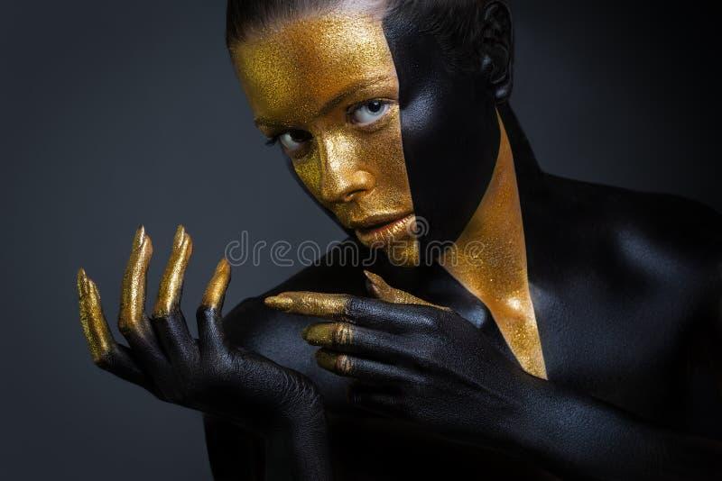 Härlig flicka med guld- och svart målarfärg på hennes framsida och kropp Kvinnlig stående med idérik makeup arkivbilder