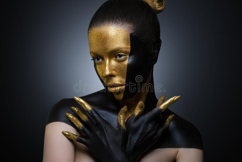Härlig flicka med guld- och svart målarfärg på hennes framsida och kropp Kvinnlig stående med idérik makeup långt royaltyfri fotografi