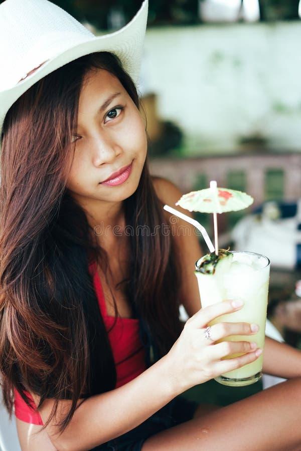 Härlig flicka med hatten och att dricka ny och uppfriskande ananasfruktsaft, semester för sommarferie arkivbilder