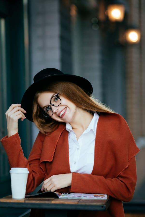 Härlig flicka med hatten och exponeringsglas med kaffe och en tidskrift royaltyfri fotografi