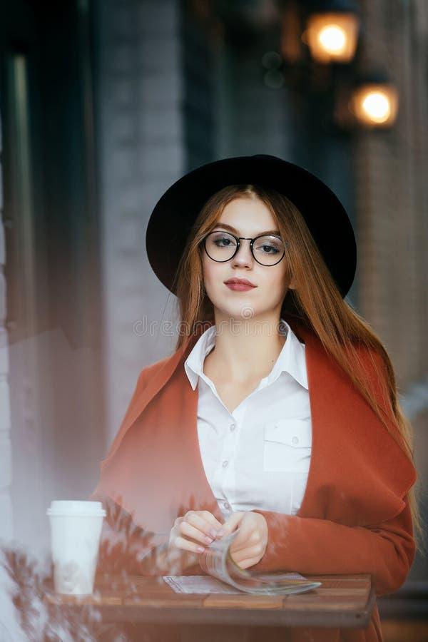 Härlig flicka med hatten och exponeringsglas med kaffe och en tidskrift royaltyfri bild