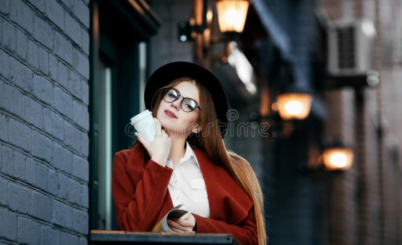 Härlig flicka med hatten och exponeringsglas med kaffe i hand fotografering för bildbyråer