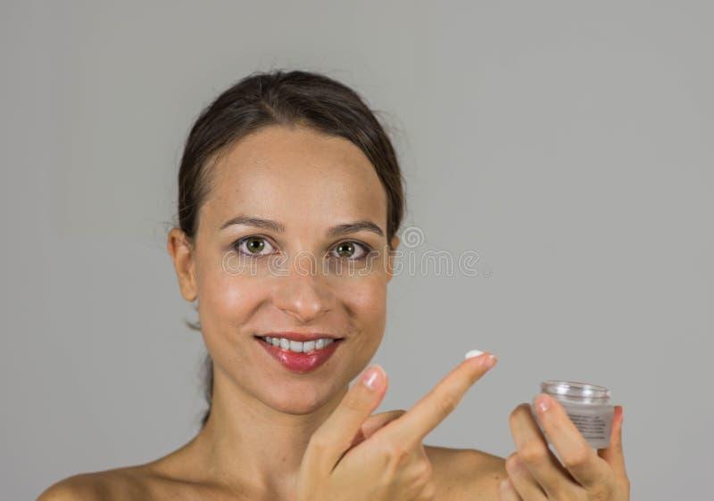 Härlig flicka med hudkräm royaltyfri fotografi