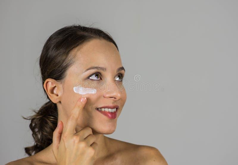 Härlig flicka med hudkräm arkivbilder