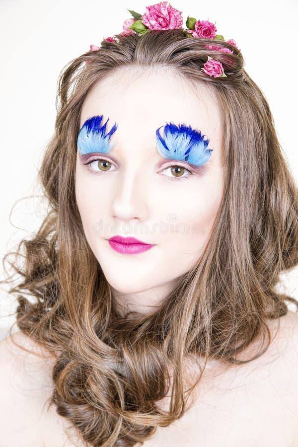 Härlig flicka med idérikt smink och frisyr med blommor arkivfoto