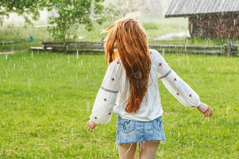 Härlig flicka med iklädd broderi för rött hår som är ukrainsk i regnet arkivbild