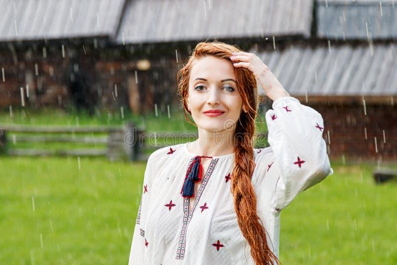 Härlig flicka med iklädd broderi för rött hår som är ukrainsk i regnet royaltyfri fotografi
