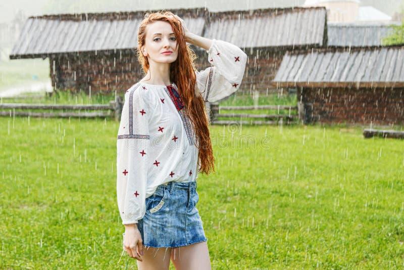 Härlig flicka med iklädd broderi för rött hår som är ukrainsk i regnet arkivfoto
