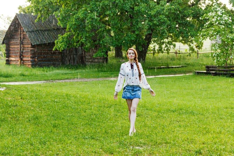 Härlig flicka med iklädd broderi för rött hår som är ukrainsk i regnet royaltyfri bild
