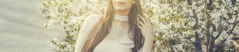 Härlig flicka med körsbärsröda blommor för vår, bakbelyst solsken royaltyfria foton