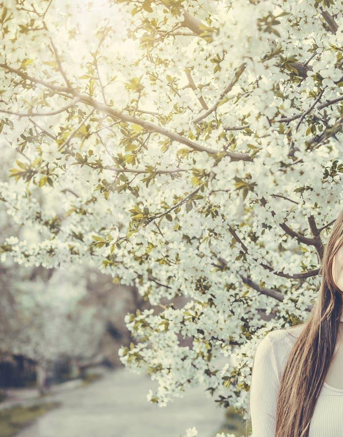 Härlig flicka med körsbärsröda blommor för vår, bakbelyst solsken arkivbilder