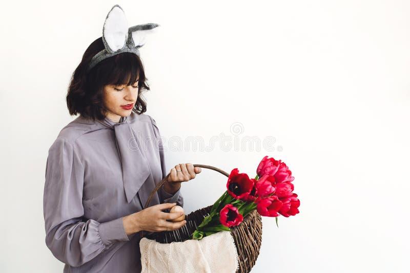 Härlig flicka med kaninöron som inomhus rymmer easter träägget och tulpan i lantlig korg på vit bakgrund, utrymme för text royaltyfri foto
