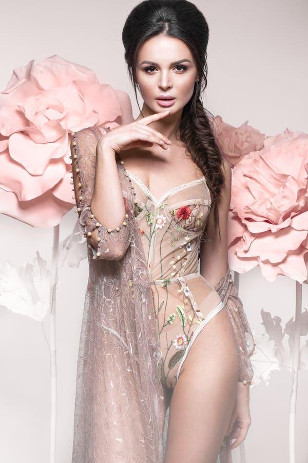 Härlig flicka med klassiskt smink och frisyr i delikat underkläder med stora blommor på bakgrund Härlig le flicka royaltyfria bilder