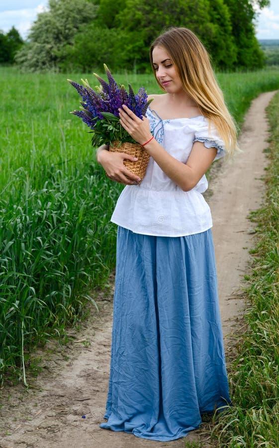 Härlig flicka med korgen av lösa blommor på den lantliga vägen royaltyfria bilder
