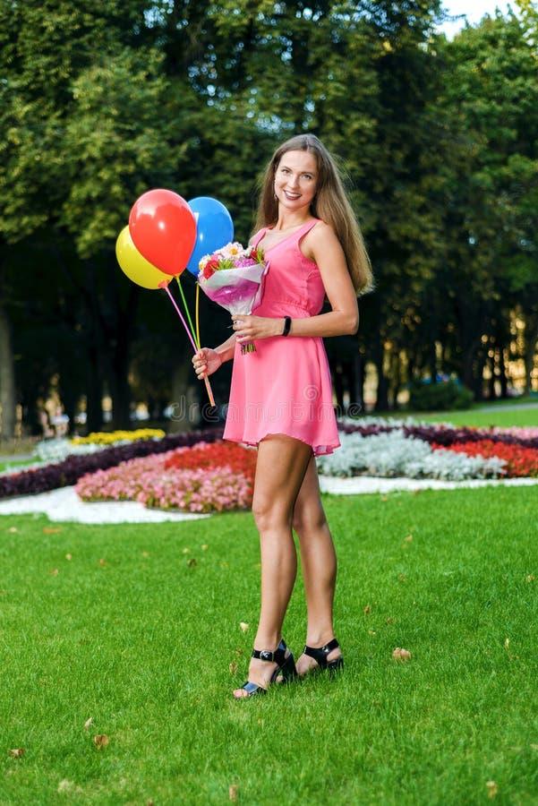 Härlig flicka med långa ben i rosa klänning royaltyfria bilder