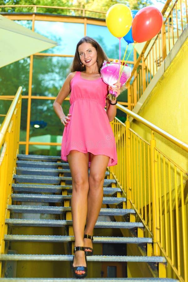 Härlig flicka med långa ben i rosa klänning med royaltyfri fotografi