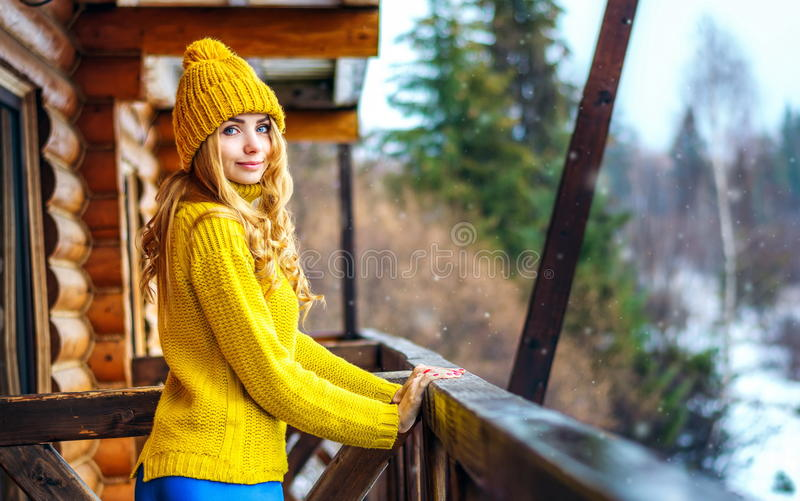 Härlig flicka med långt blont lockigt hår i en rät maskatröja och hatt arkivfoto