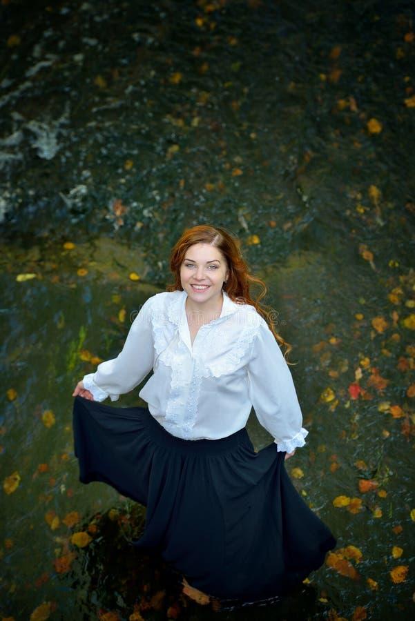 Härlig flicka med långt hår i den vita skjortan och svart kjoldans i floden med höstsidor som ser upp och ler arkivbild