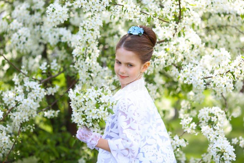Härlig flicka med långt hår i en blommande trädgård royaltyfria bilder
