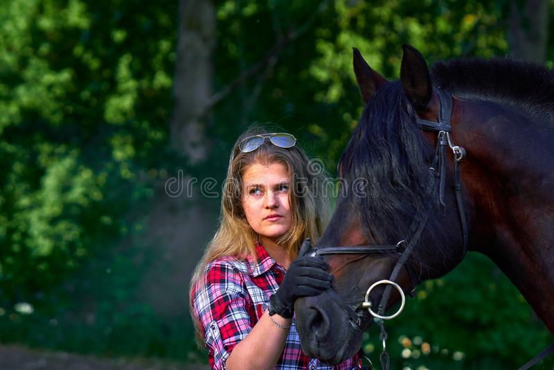 Härlig flicka med långt hår på en gå med en häst arkivfoton