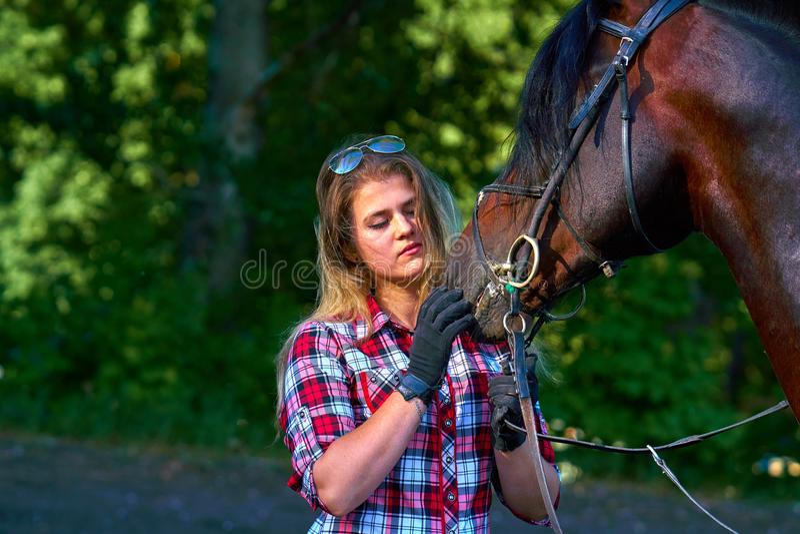 Härlig flicka med långt hår på en gå med en häst arkivfoto