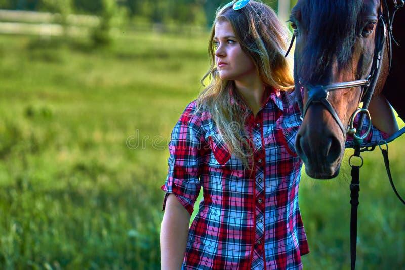 Härlig flicka med långt hår på en gå med en häst arkivbild