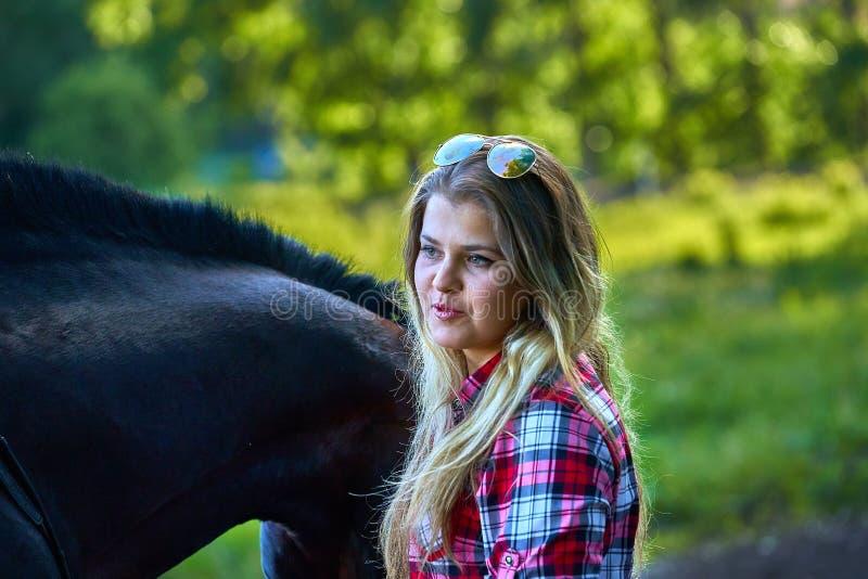 Härlig flicka med långt hår på en gå med en häst royaltyfri fotografi