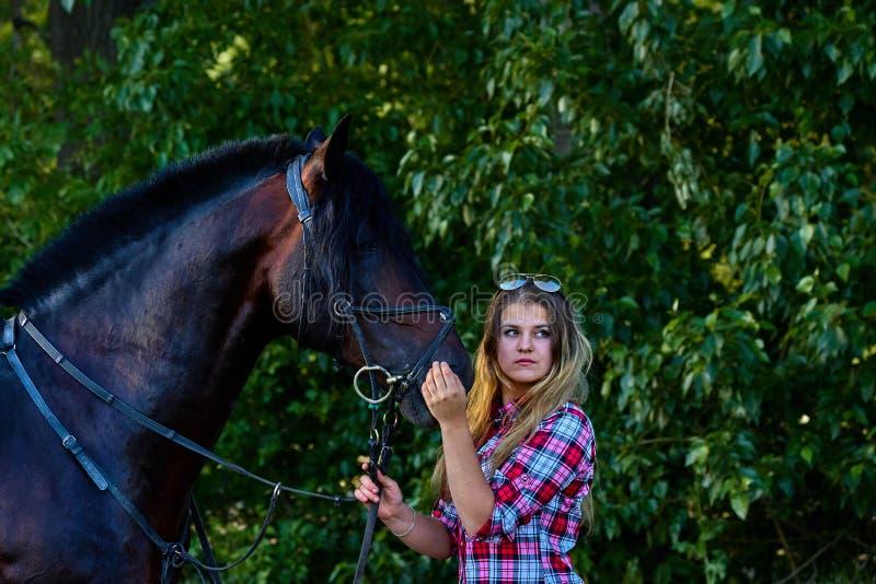Härlig flicka med långt hår på en gå med en häst arkivbilder