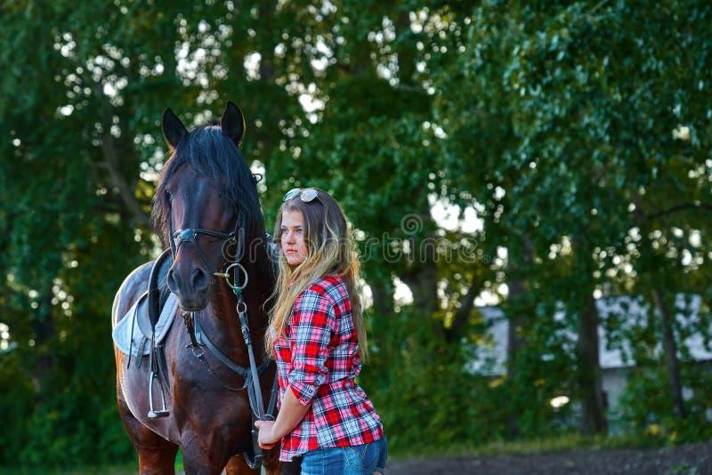 Härlig flicka med långt hår på en gå med en häst fotografering för bildbyråer