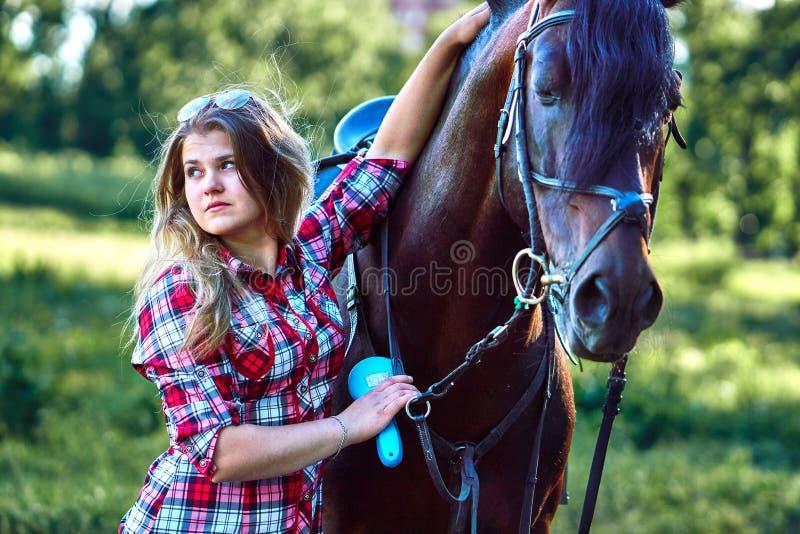 Härlig flicka med långt hår på en gå med en häst royaltyfri bild