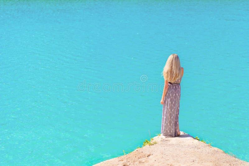 Härlig flicka med långt vitt hår i ett långt klänninganseende på kusten av sjön med blått vatten i en solig ljus dag royaltyfri foto