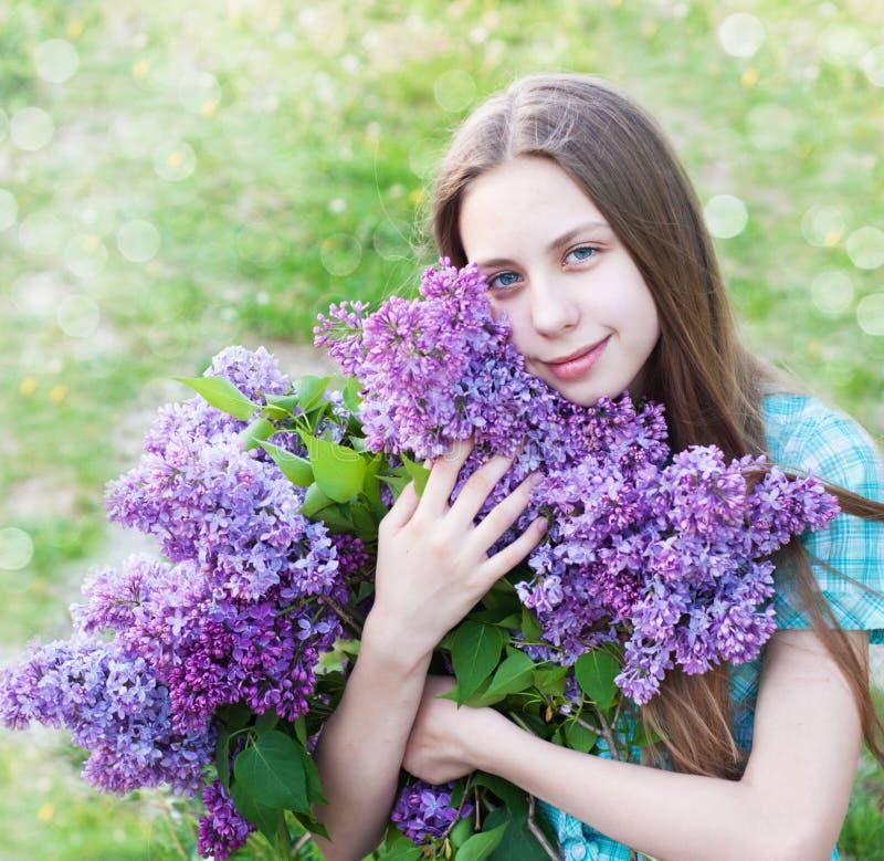 Härlig flicka med lila blommor royaltyfri foto