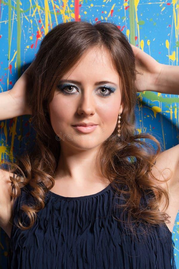 Härlig flicka med ljus makeup och långt krullat hår på multic arkivbild
