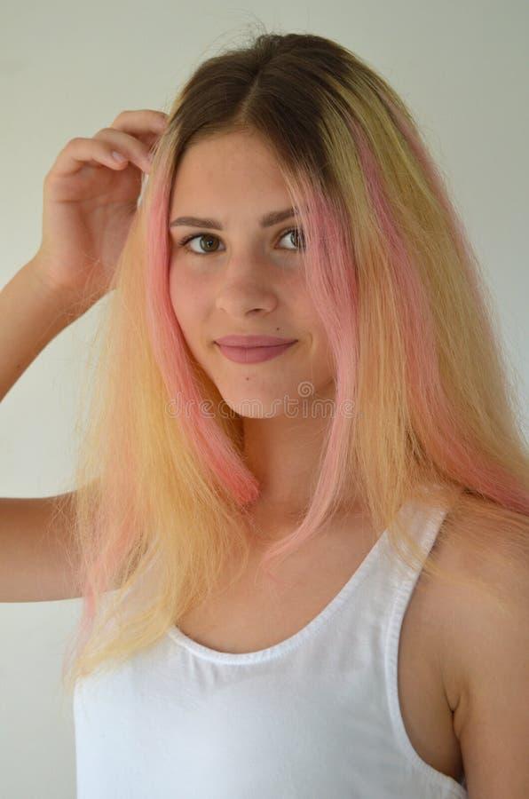 Härlig flicka med ljust långt hår, med rosa lås fotografering för bildbyråer