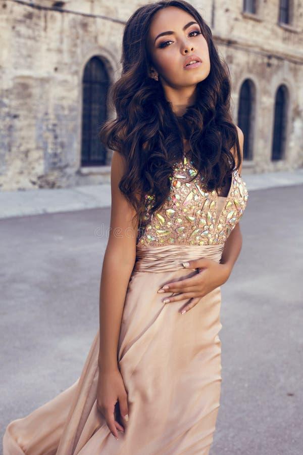 Härlig flicka med mörkt hår i lyxig klänning royaltyfria bilder