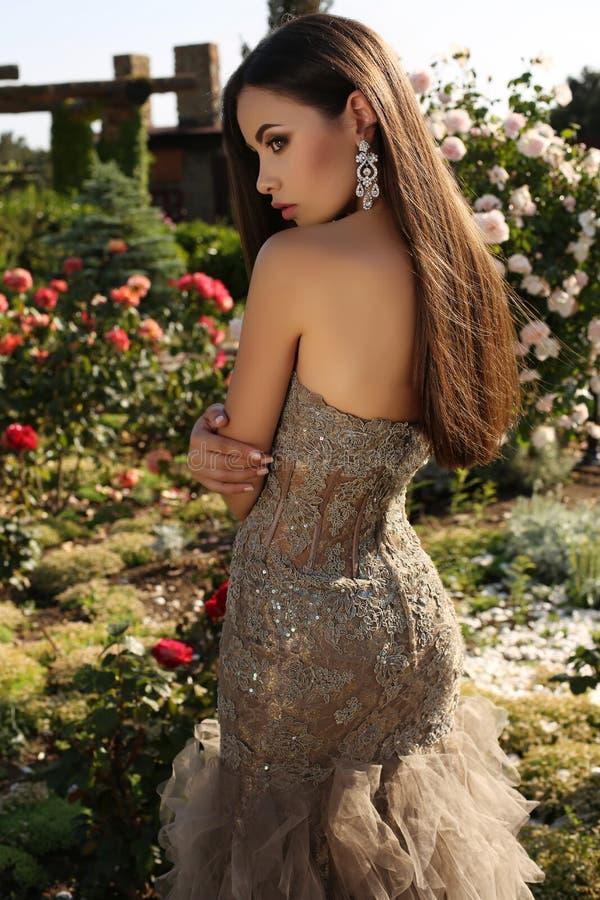 Härlig flicka med mörkt hår i lyxig paljettklänning royaltyfri foto